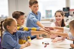 Enfants heureux tenant des mains à l'école de robotique Images libres de droits