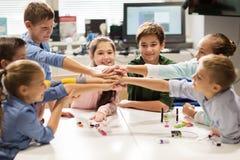 Enfants heureux tenant des mains à l'école de robotique Image libre de droits