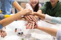 Enfants heureux tenant des mains à l'école de robotique Image stock