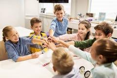 Enfants heureux tenant des mains à l'école de robotique Photographie stock