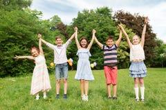 Enfants heureux tenant des mains en parc d'été Photo stock