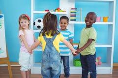 Enfants heureux tenant des mains ensemble Photos stock