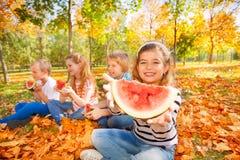 Enfants heureux tenant la pastèque et la consommation Photographie stock