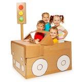 Enfants heureux voyageant en voiture de carton photos stock