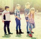 Enfants hopscotching et souriant dans le terrain de jeu Photo stock