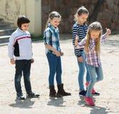 Enfants hopscotching et souriant dans le terrain de jeu Photos stock