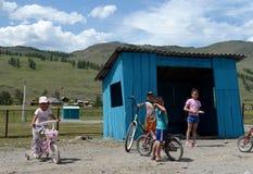 Enfants inconnus à l'arrêt d'autobus au centre de secteur Ulagan de la République d'Altai images libres de droits