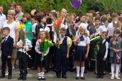Enfants inscrits dans la premi?re classe avec des bouquets des fleurs et des ballons dans les mains, les professeurs et les ?tudi photo libre de droits