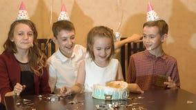 Enfants insouciants à une fête d'anniversaire les amis ont trempé le visage de fille d'anniversaire dans le gâteau d'anniversaire Photographie stock