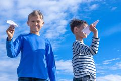 Enfants jetant l'avion de livre blanc Photographie stock