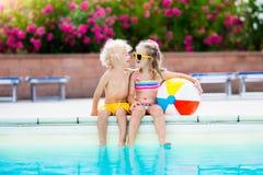 Enfants jouant à la piscine extérieure Photo libre de droits
