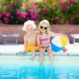 Enfants jouant à la piscine extérieure Photo stock