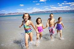 Enfants jouant à la plage Photos libres de droits