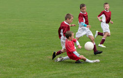 Enfants jouant au football Photo stock