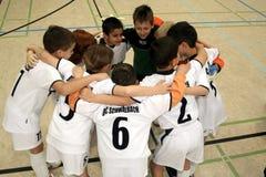 Enfants jouant au football dans un hall d'intérieur Photographie stock