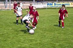 Enfants jouant au football en été Image stock