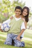 Enfants jouant au football en stationnement Photos stock