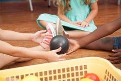 Enfants jouant avec des boules de plastiques Image stock