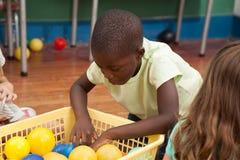Enfants jouant avec des boules de plastiques Images stock