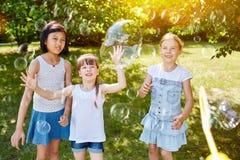 Enfants jouant avec des bulles de savon en été Photos libres de droits