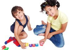 Enfants jouant avec des cubes dans le spac d'isolement blanc Image libre de droits