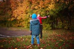 Enfants jouant avec des feuilles en parc Photographie stock
