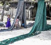 Enfants jouant avec des filets de poissons à Zanzibar images libres de droits