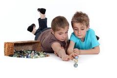 Enfants jouant avec des marbres photo stock