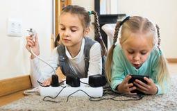 Enfants jouant avec des prises et l'électricité à l'intérieur Images libres de droits