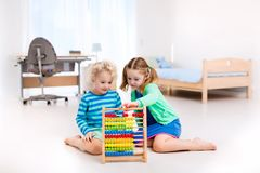 Enfants jouant avec l'abaque en bois jouet éducatif Photo libre de droits