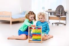 Enfants jouant avec l'abaque en bois jouet éducatif Image stock
