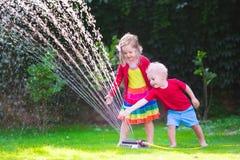 Enfants jouant avec l'arroseuse de jardin Images stock