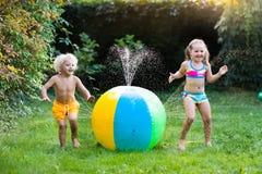Enfants jouant avec l'arroseuse de jouet de boule de l'eau Photos libres de droits