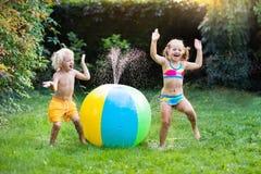 Enfants jouant avec l'arroseuse de jouet de boule de l'eau Photos stock