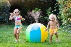 Enfants jouant avec l'arroseuse de jouet de boule de l'eau Photographie stock libre de droits