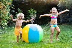 Enfants jouant avec l'arroseuse de jouet de boule de l'eau Photo stock