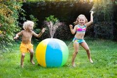 Enfants jouant avec l'arroseuse de jouet de boule de l'eau Photographie stock
