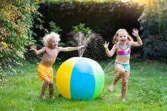 Enfants jouant avec l'arroseuse de jouet de boule de l'eau Images libres de droits