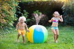 Enfants jouant avec l'arroseuse de jouet de boule de l'eau Photo libre de droits