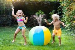 Enfants jouant avec l'arroseuse de jouet de boule de l'eau Image libre de droits