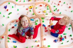 Enfants jouant avec l'ensemble en bois de train Image stock