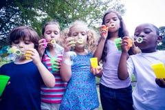 Enfants jouant avec la baguette magique de bulle en parc Photo libre de droits