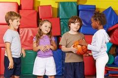 Enfants jouant avec la boule dans le gymnase Photo stock