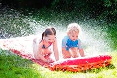 Enfants jouant avec la glissière d'eau de jardin Photographie stock libre de droits
