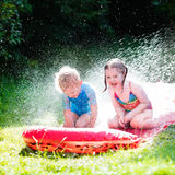 Enfants jouant avec la glissière d'eau de jardin Image libre de droits