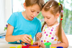 Enfants jouant avec la pâte de jeu Photographie stock libre de droits