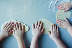 Enfants jouant avec la pâte sur le fond bleu images stock