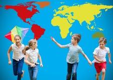 Enfants jouant avec le cerf-volant et le fonctionnement devant la carte colorée du monde Image stock