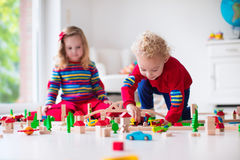 Enfants jouant avec le chemin de fer et le train de jouet Image stock