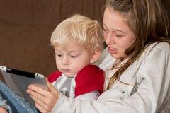 Enfants jouant avec le comprimé Image libre de droits